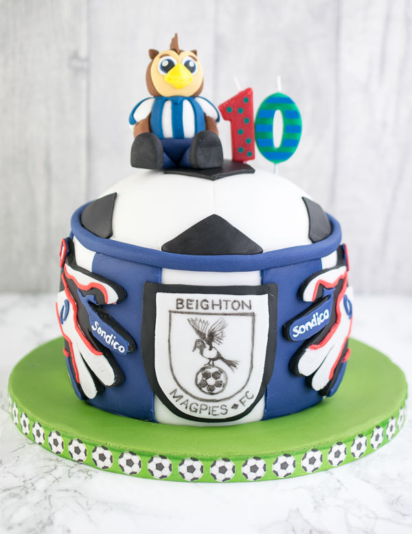 A chocolate fudge cake for a football fan complete with the mascto from his main team, the badge from the team he played in and replica goalie gloves