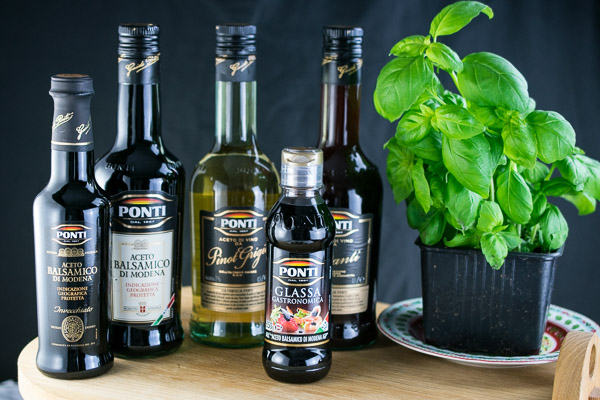 A selection of Ponti vinegars and balsamic glaze with a large bush of fresh basil.