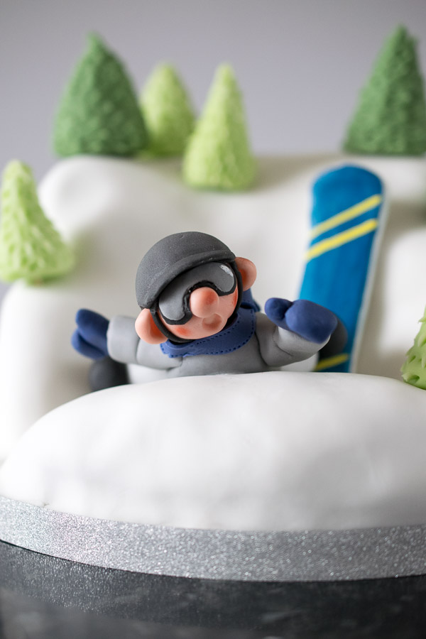 Snowboarder cake - poor little guy has fallen off his board but his fall was broken by a chocolate and vanilla marble cake hill!