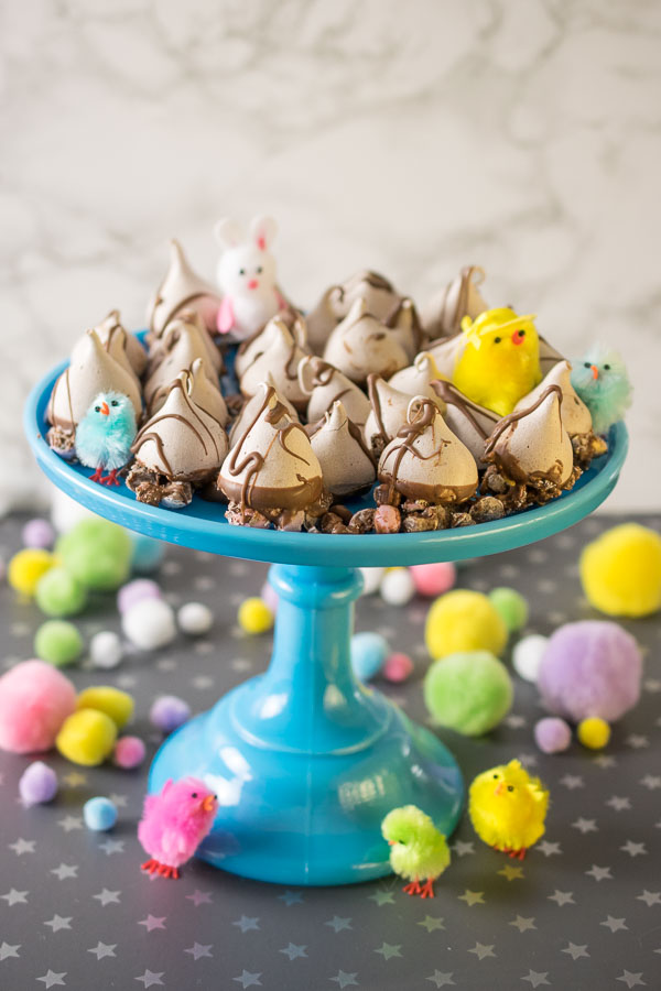 A blue milk glass cake stand filled with Mini Egg Meringue Kisses and decorated with neon fluffy chicks and white fuzzy bunnies!